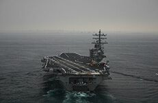 aircraft carrier, the uss ronald reagan returning to port after a deployment, the sailors are manning the rails.